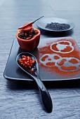 Gefüllte Paprikaschote mit Wildreis, Chili und Tomate, Löffel mit Chiliringen und schwarzer Teller mit Abdrücken von Paprikapulver