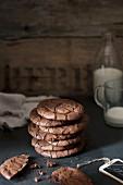 Gestapelte Schokoladenkekse, Milchflasche und Milchglas