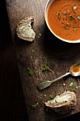 A bowl of fresh tomato soup with slices of buttered bread, fresh basil an spoon.