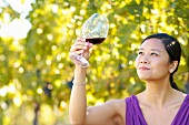 Oriental woman with glass of Burgundy red wine in a vineyard.