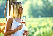 Junge Frau trinkt ein Glas Rosewein auf der Terrasse