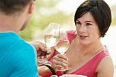 Paar trinkt Weisswein bei einem Picknick am Strand
