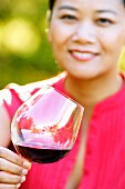 Oriental woman drinking red wine in a vineyard.