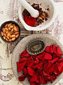 A stone bowl filled with rose petals, a bowl of almonds and a porcelain mortar