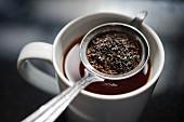 Teesieb mit Teeblättern in einer Teetasse