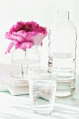 A pink rose in a glass of water next to a bottle of water