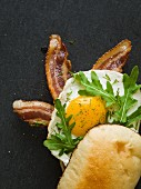 Breakfast sandwich with bacon, egg and arugula exposed sitting on a black slate cutting board