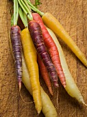 Multi-colored carrots in white, yellow, orange and red on a worn cutting board