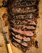 London Broil Steak auf Schneidebrett mit karamellisierten Zwiebeln