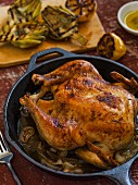 Whole roasted chicken in a cast iron pan on a rustic surface with grilled baby artichokes and lemon in the background