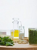 Pesto in a jar with individual ingredients of basil, garlic, pine nuts, romano cheese, sea salt and olive oil