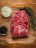 Frisches Steak auf braunem Papier mit Rosmarin, Zwiebeln und schwarzen Pfefferkörnern