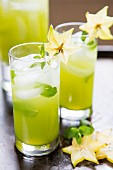 Two cocktails garnished with star fruit and peppermint