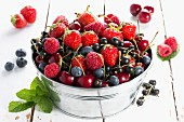 Various red fruits in a metal bucket