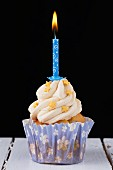 A cupcake decorated with gold stars and a birthday candle