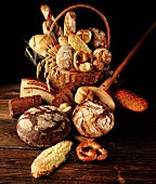 Various types of bread and rolls in a basket with ears of wheat