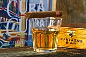 A Cuban cigar balanced on a glass of rum