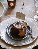 Small chocolate cake and name tag on festively set table