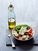 A Greek salad next to a bottle of olive oil