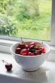 Schale mit Kirschen auf der Fensterbank