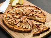 Apple tarts made with finely sliced apples on a chopping board