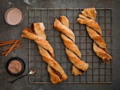 Cinnamon twist pastries on a cooling rack, cinnamon sticks and cinnamon-sugar