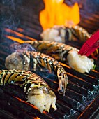 Halved lobster tails on a barbecue