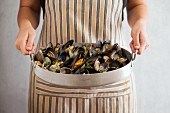 A person wearing a striped apron holding a roasting tin of mussels and clams garnished with parsley