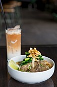 Noodles with pork and a cocktail made with coconut milk
