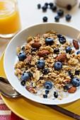 Frühstücksmüsli mit Mandeln und Blaubeeren; dazu Orangensaft