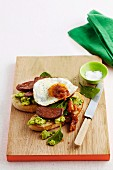 Toasted bread topped with chorizo, fried egg and avocado cream