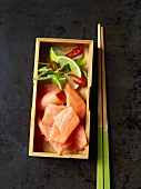 Salmon sashimi with limes in a wooden box (Japan)