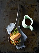 Salmon fillet with lentils on a spoon next to a little jug of soy sauce