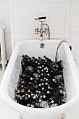 A bathtub filled with bottles of beer and ice