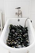 Bierflaschen und Eis in einer Badewanne