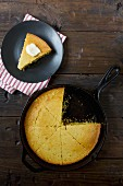 Cornbread in a frying pan and a slice of cornbread with butter