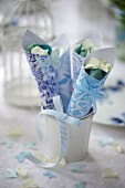 Blau-weiss gemusterte Papiertüten mit Blütenblättern für eine Hochzeit