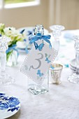 Number tag tied to glass bottle on wedding reception table