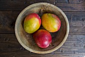 Ripe mangos in a wooden bowl