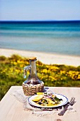 Sardines with olive oil and lemons on a table by the sea