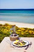 Sardinen mit Olivenöl & Zitronen auf Tisch am Meer