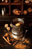 Hot buttered rum in a pewter mug with vanilla, cinnamon, star anise and ground spices