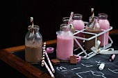 Chocolate milk and raspberry milk in mini bottles with liquorice sweets on a chalkboard