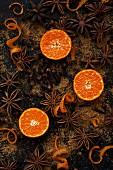 Mandarinenhälften, spiralförmige Orangenschalen, Sternanis und Gewürznelken