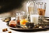 Various baking ingredients in glasses (flour, egg, brown sugar, milk) and old-fashioned cake tins on tray