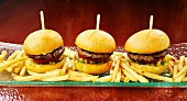 Three mini burgers with chips on a long serving platter