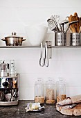 Coffee machine, glass storage jars, bread and butter on worksurface below cooking utensils, containers and tongs on wall-mounted shelf