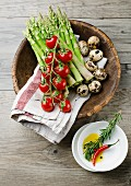 Green asparagus, tomatoes and quail's eggs in a wooden bowl