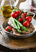 Beef steak with asparagus and tomatoes