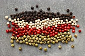 Rows of different coloured peppercorns